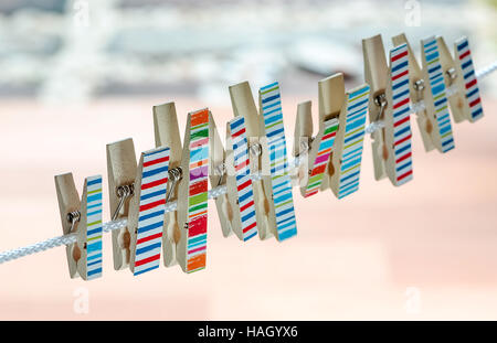 Colorful of wooden clothespins on a rope - Stock Photo