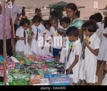 Group of school children looking at toy stall on Galle face Green,Colombo,Sri Lanka. - Stock Photo