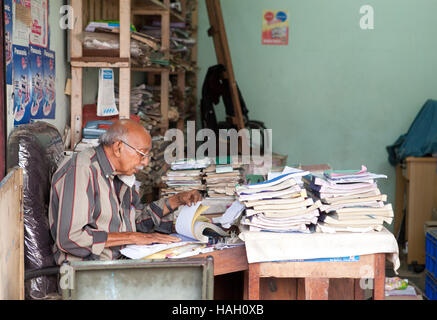 Elderly man sitting at a desk doing his paperwork,India. - Stock Photo