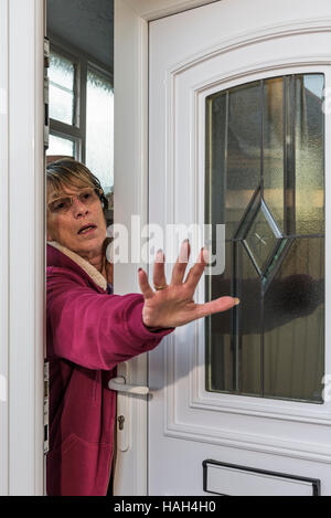 Lady attempting to push away an intruder. - Stock Photo