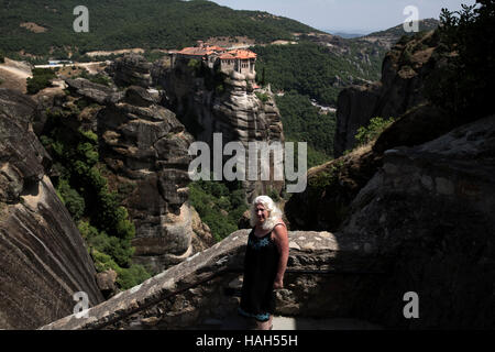 A tourist at the Great Meteoron Monastery, Meteora, Greece on July 15, 2016. The Varlaam monastery seen at the background - Stock Photo