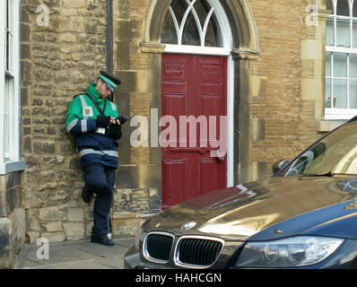 A traffic warden issues a parking ticket in Stamford England UK - Stock Photo