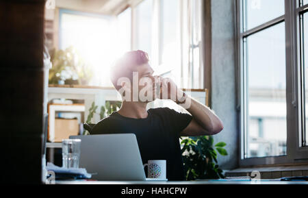 Shot of young man sitting at his office talking on cell phone. Business man working at his desk with laptop making - Stock Photo
