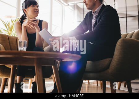 Shot of business man showing something on digital tablet to his female colleague. Business people meeting in office - Stock Photo