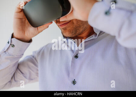 Closeup shot of young man using Virtual Reality glasses. Businessman wearing VR goggles. - Stock Photo