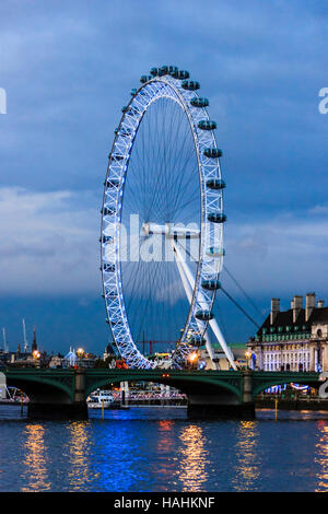 The London Eye lit up at night, seen from across the River Thames on the Victoria Embankment, London, UK - Stock Photo
