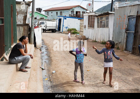 two children talking to an adult on the street, Imizamo Yethu township, Cape Town, South Africa
