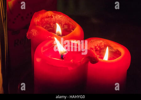 Three red candles burning in the dark - Stock Photo