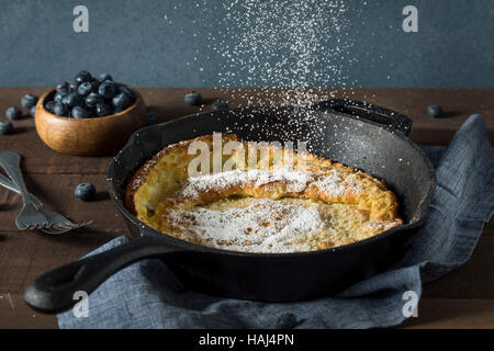 Homemade Dutch Baby Pancake with Blueberries and Powdered Sugar - Stock Photo