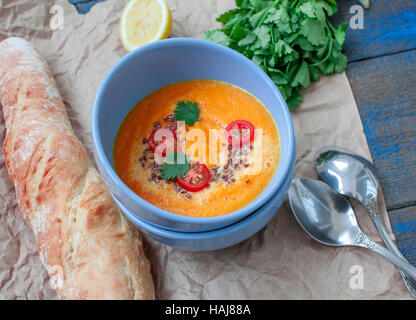 Vegan orange vegetable soup (carrots, sweet potatoes, pumpkin) with herbs and coconut cream.  Perfect for the detox - Stock Photo