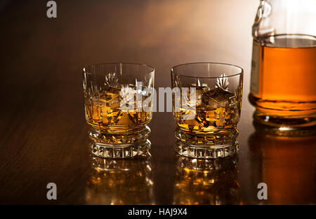 Whiskey with ice in glasses, rustic wood background. - Stock Photo