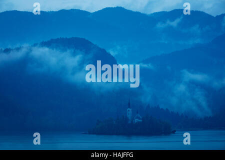 Misty morning over the Pilgrimage Church of the Assumption of Maria, Bled, Upper Carniola, Slovenia - Stock Photo