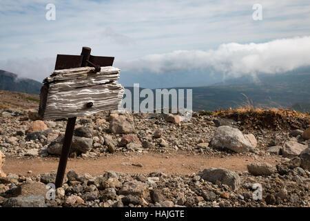 Weather beaten wooden signpost next to dirt path, Daisetsuzan, Hokkaido, Japan - Stock Photo