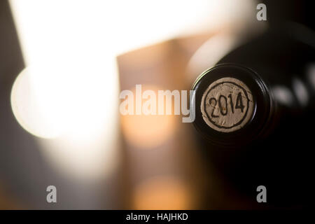 Close-up of closed wine bottles lying on blurry background, winery - Stock Photo