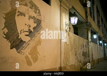 Mural of Che Guevara on wall of waterside  terminal de la Sierra Maestra old custom offices lit by street lamps,dawn - Stock Photo