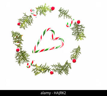 Christmas composition. Wreath made of green thuja twigs, red wild rose fruits and candy canes on white background. - Stock Photo