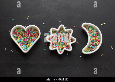 Cookie cutters with candy sprinkles - Stock Photo