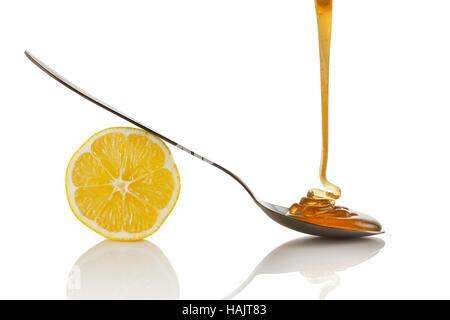 Lemon slice and honey flowing on spoon - Stock Photo