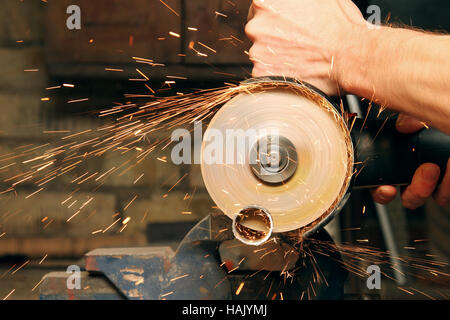cutting metal with angle grinder, sparks from the disk - Stock Photo