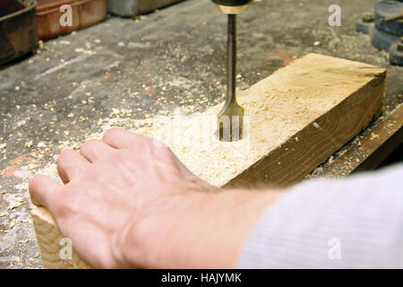 carpenter drilling in a wooden board - Stock Photo