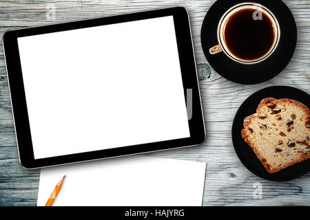 workplace with digital tablet, notebook, cake and coffee cup - Stock Photo