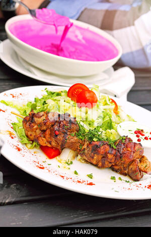 grilled shashlik with vegetables on white plate - Stock Photo