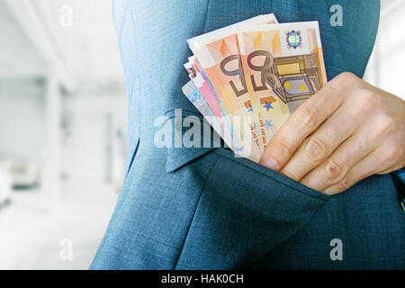 corruption concept, man putting money in jacket pocket - Stock Photo