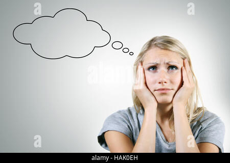 pensive woman with blank thought bubble on gray background - Stock Photo