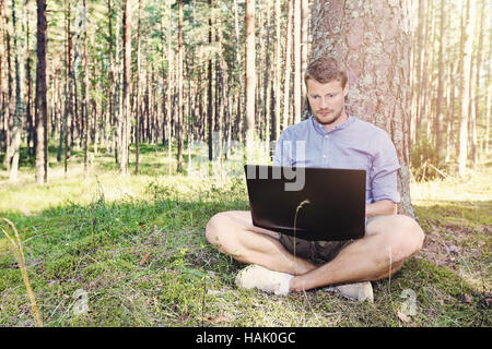 young man working with his laptop outdoors in nature - Stock Photo