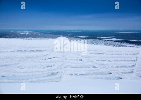 frozen fence covered with snow against mountains background - Stock Photo