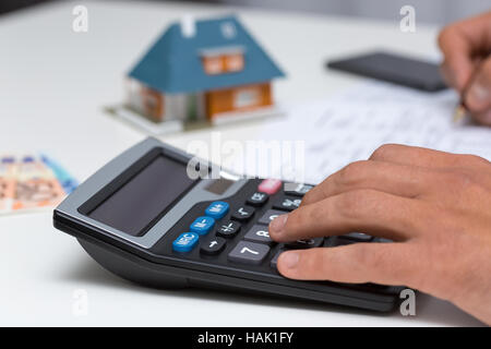 hand on calculator - calculating household expenses - Stock Photo