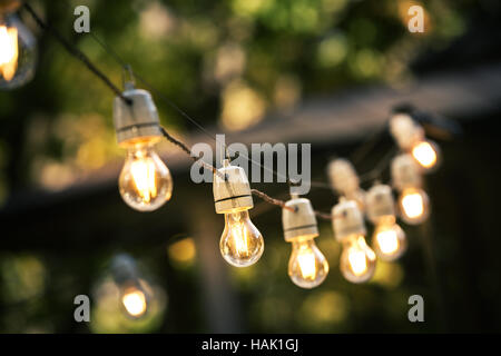 outdoor string lights hanging on a line in backyard - Stock Photo