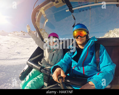 happy couple taking selfie in chairlift at ski resort - Stock Photo