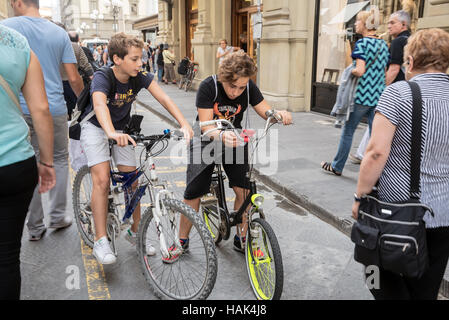 Street scene : two boys on bikes, Florence, capital of Tuscany region, Italy - Stock Photo