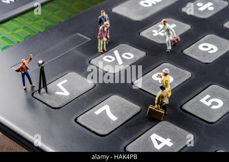 business concept, closeup of miniature figurine of businessmen discussing on big black calculator about interest - Stock Photo