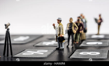 business concept, closeup of miniature figurine of people queuing on big black calculator for better mortgage interest - Stock Photo