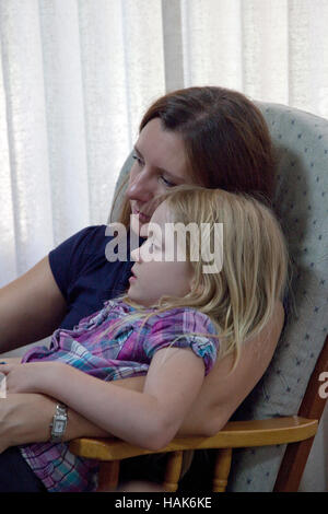 Mother totally absorbed listening to daughter in living room chair, age 33 and 5.  Champlin Minnesota MN USA - Stock Photo