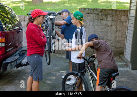 Family packs bicycles on back of SUV truck for transport to start of bike ride. Clitherall Minnesota MN USA - Stock Photo