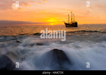 Ocean sunset ship is an old pirate ship out at sea with full flags flying as the sun sets in an orange color filled - Stock Photo