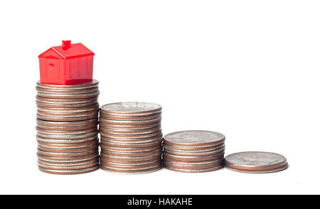 Toys house and pile of coins representing financial goal of home ownership - Stock Photo