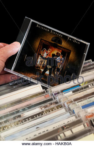 Ta-Dah, Scissor Sisters 2nd CD being chosen from among rows of other CD's - Stock Photo