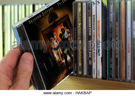 Ta-Dah, Scissor Sisters 2nd CD being chosen from a shelf of other CD's - Stock Photo