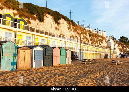 England, Broadstairs. Dawn. View along Beach huts with terrace of same above, on the empty beach in the golden hour - Stock Photo