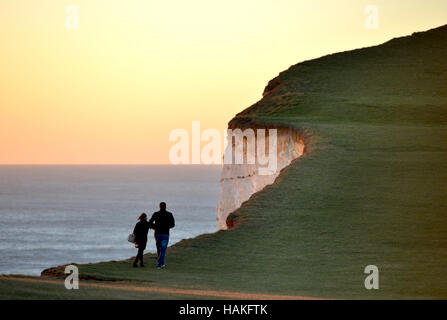 Couple walking near to the cliff edge at Beachy Head, famous suicide spot in East Sussex. - Stock Photo