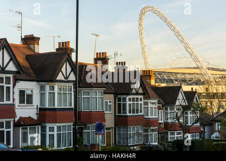 The arch of Wembley Stadium seen over the roofs of suburban houses Wembley, London. - Stock Photo