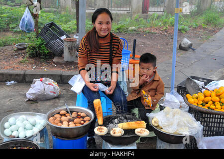 Vendors, such as this mother and son, often sale food along the roadway in some areas of China. - Stock Photo