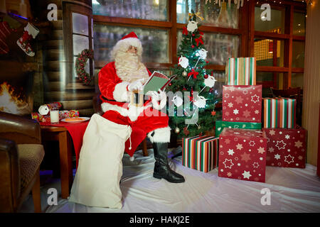Santa in grotto christmas display   lighted christmas tree, presents,fireplace,stockings gifted wrapped reading - Stock Photo