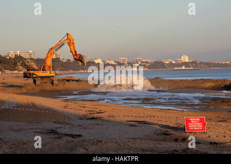 Beach replenishment work in action at Branksome / Poole in low winter sunshine. Bournemouth seafront backdrop. - Stock Photo
