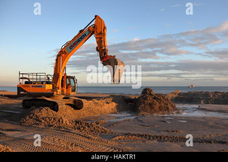 Beach replenishment work in action at Branksome / Poole in low winter sunshine. - Stock Photo