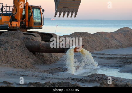 Beach replenishment work in action at Branksome / Poole in low winter sunshine and IOW backdrop. - Stock Photo